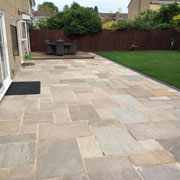 indian stone paving and a grassy garden