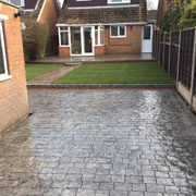 grey cobbled drive, with a lawn and house