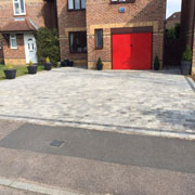 light grey cobbled driveway and red garage door on a red brick house