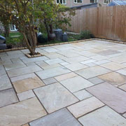 a stone patio with a tree